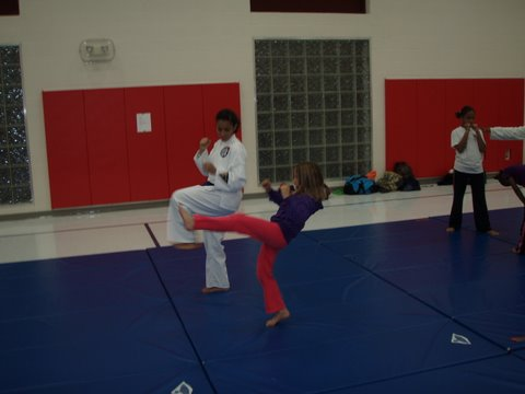Erika Tucker-Owens working with new student Nia on basic kicks